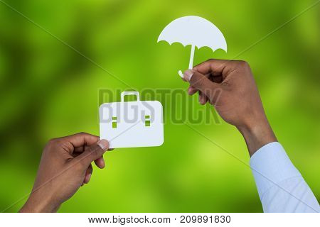 hands holding a schoolbag and an umbrella in paper against trees in forest