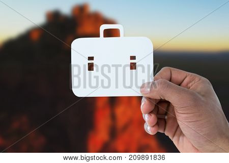 hand holding a schoolbag against tranquil view of rocky mountains