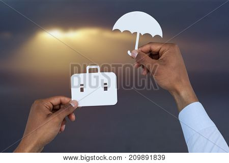 hands holding a schoolbag and an umbrella in paper against scenic view of sea