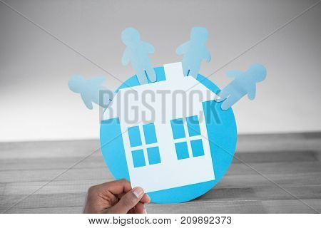 hand holding a house in paper against blue paper cut out figures on globe