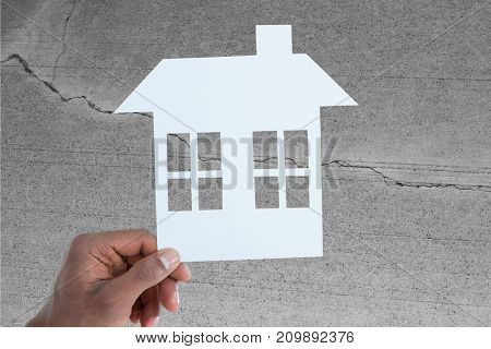 hand holding a house in paper against concrete wall with crack