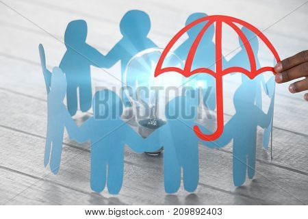 hand holding a red umbrella against blue paper figures standing around light bulb on wooden table
