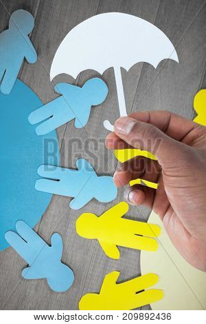 hand holding an umbrella in paper against blue and yellow paper cut out figures on wooden table