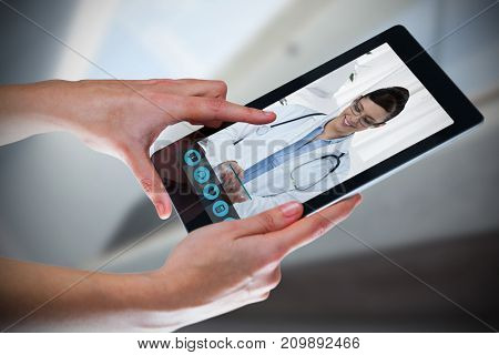 Hands using digital tablet against white background against bright white room with windows