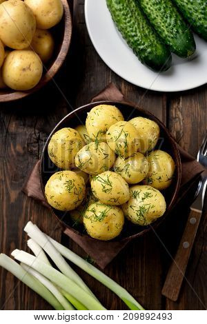 Young boiled potatoes with dill in bowl on wooden background top view