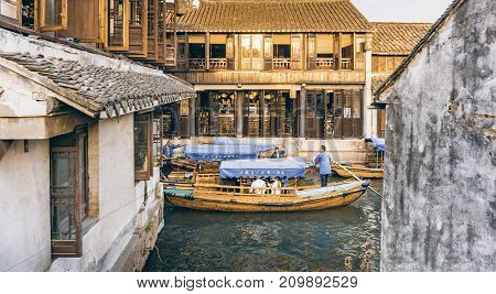 Suzhou, China - Nov 5, 2016: Several tourist boats maneuver a narrow part of the waterway at the historic Zhouzhuang Water Town.