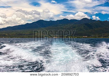 A speedboat departs from the port of Lombok and leaves a wave with foam against the backdrop of Mount Rinjani. Lombok island, Indonesia.