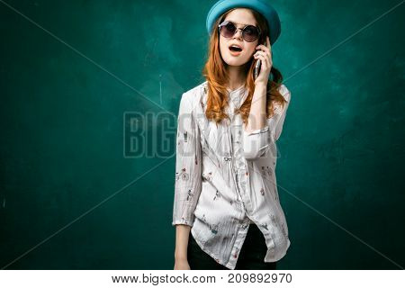 cheerful girl in a turquoise hat and wearing sunglasses flaunts on the phone