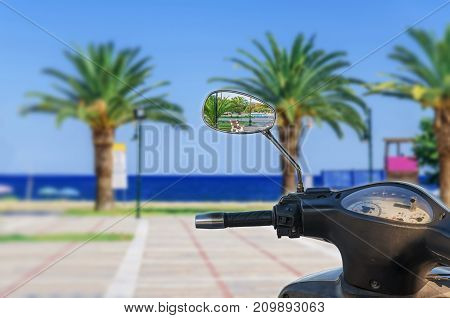 Motor bike mirror reflection with blurry sea background