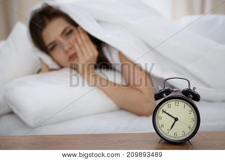 Beautiful sleeping woman lying in bed and trying to wake up with alarm clock. Girl having trouble with getting up early in the morning, Nightmare. poster