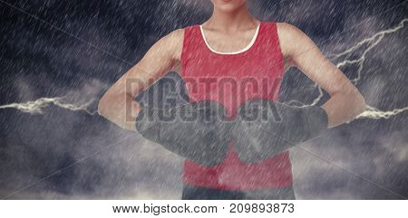 Close-up mid section of a determined female boxer against splashing of blue color powder