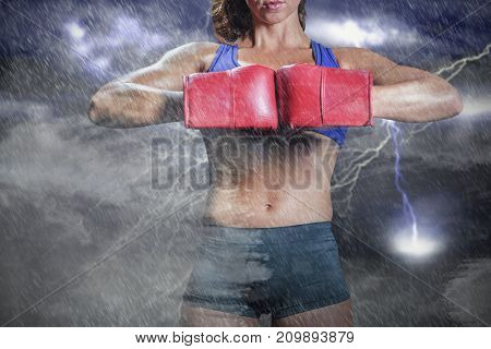 Midsection of boxer flexing stance against splashing of blue and yellow color powder