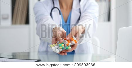 Female doctor hand holding pack of different tablet blisters closeup. Life save service, legal drug store, prescribe medicament, blood pressure, disease healing concept.