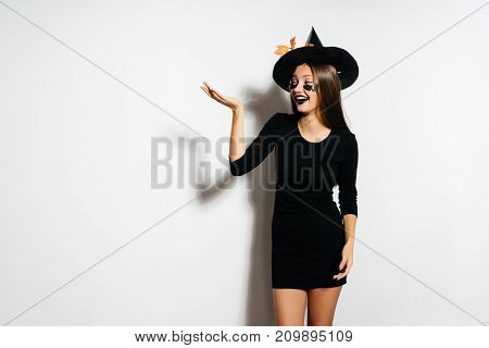 a young beautiful gothic girl in the shape of a witch in halloween, a big black hat decorated with yellow leaves,