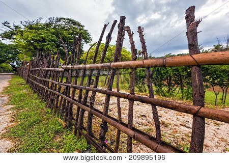 A fence made of bamboo wood and brown twisted curves on the background of a littered yard with green trees in cloudy weather. Branch fence closeup, Gili Trawangan, Indonesia.