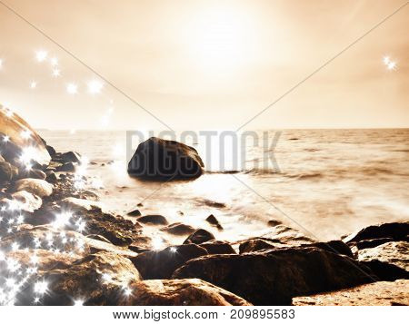Boulders At Island Shore Stick Up From Smooth Sea. Stony Coast Defies To Waves Of Ocean