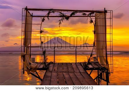 Wedding gazebo on the background of the setting sun behind Gunung Agung. Canopy for romantic photo shoots, Gili Trawangan, Indonesia.