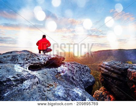 Adult Tourist In Black Trousers, Red Jacket And Dark Cap Sit On Cliff Edge And Looking To Valley