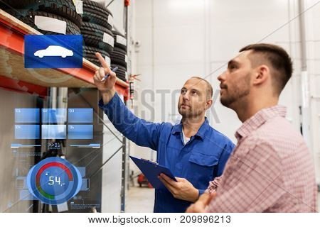 auto service, repair, maintenance and people concept - mechanic with clipboard showing tire to man at car shop