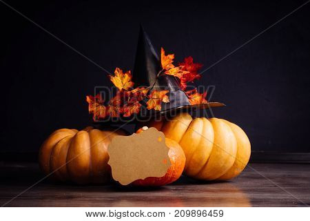 a composition for decorating a house for halloween, lie yellow and orange pumpkins, a big black witch hat and yellow leaves