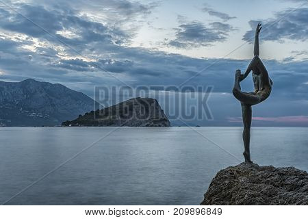 BUDVA MONTENEGRO - October 01 2017: Beautiful and elegant sculpture of a gymnast located on a rocky rock near the beach Morgen and the old town of Budva in Montenegro.
