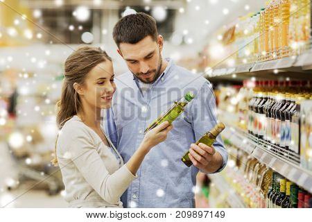 shopping, food, sale, consumerism and people concept - happy couple buying olive oil at grocery store or supermarket over snow