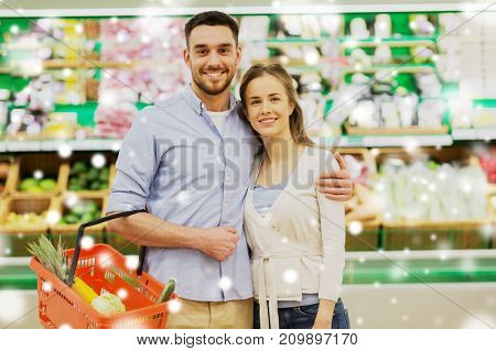shopping, sale, consumerism and people concept - happy couple with food basket at grocery store or supermarket over snow