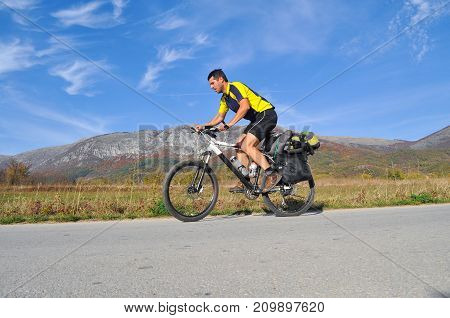 Traveler rides a bicycle on road under a mountain. Cyclist on the road on sunny autumn day