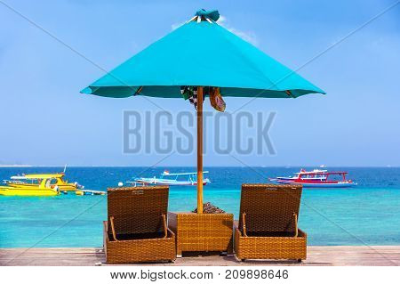 Designer lounges under the umbrella against the sea with boats. Life and interior items of the Gili Trawangan island, Indonesia.