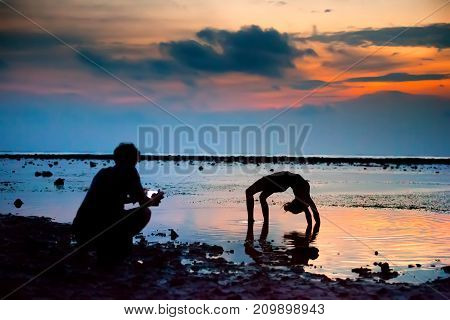 The girl shows the figures standing in the bridge on hands with a bent back the guy shoots video on the smartphone against the sunset at the sea. Gili Trawangan island, Lombok, Indonesia.