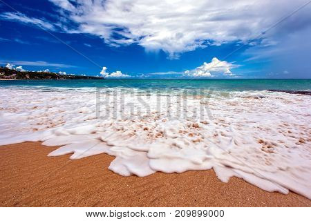 Sea white foam on the sand close-up. Sunny weather with a blue sky and a big white cloud. Foamy Wave on Dreamland beach, Bali, Indonesia.