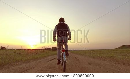 Boy teenager riding a bicycle. Boy teenager riding a bicycle goes to nature along path steadicam video shot motion