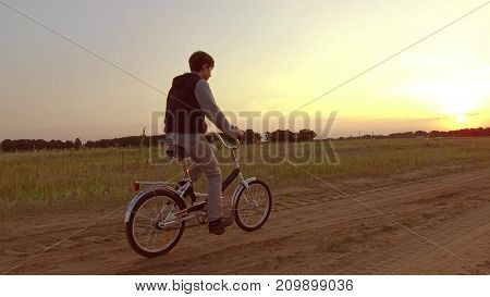 Boy teenager riding a bicycle. Boy teenager riding a bicycle goes to nature along path video steadicam shot motion