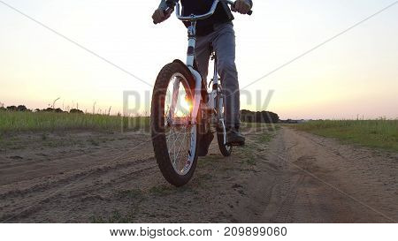 Boy teenager riding a bicycle. Boy teenager riding bicycle goes to nature along path steadicam shot motion video