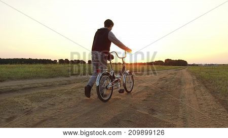 Boy teenager riding a bicycle. Boy teenager riding bicycle goes nature along path steadicam shot motion video