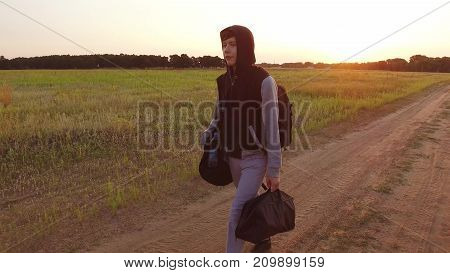 Boy teen traveling. Boy teenage tramp walking along the road in hood with backpacks a sad traveler