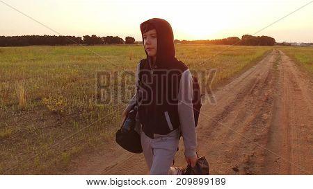 Boy teen traveling. Boy teenage tramp walking along the road in a hood with backpacks sad traveler video steadicam shot motion