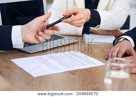 Business woman giving pen to businessman ready to sign contract. Success communication at meeting or negotiation.