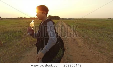 Boy teenager tourist drinking water from plastic bottle in nature. Boy homeless vagabond drink water thirst
