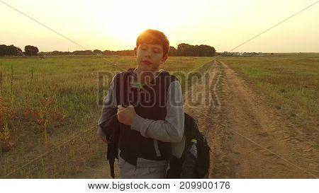 Boy teen traveling. Boy teenage tramp walking along the road in hood with backpacks sad traveler video steadicam shot motion