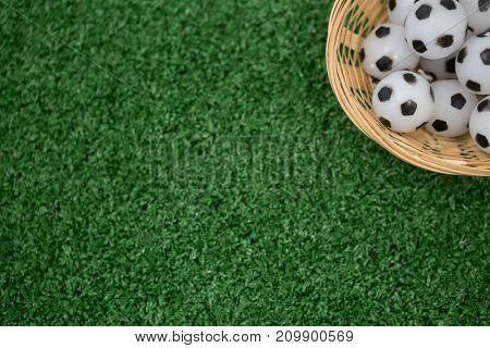 Overhead view of footballs in wicker basket on artificial grass