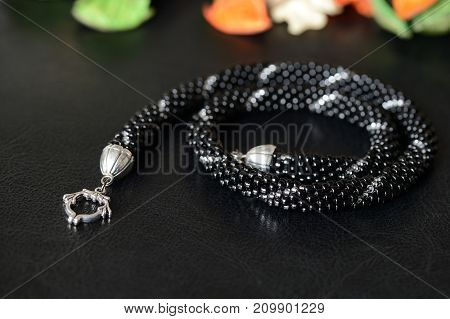 Black Beaded Necklace With Silver Line On A Dark Background