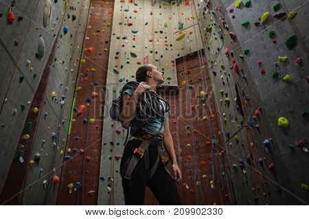 Low angle view of female athlete carrying rope looking up while standing in gym