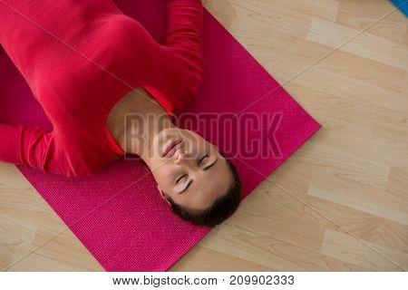 High angle view of young woman exercising while lying on mat in yoga studio