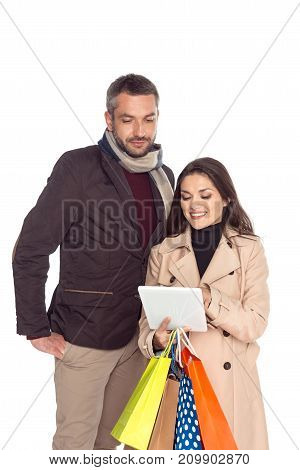 couple with digital tablet and shopping bags isolated on white