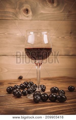 Glass Of Red Wine And Grapes On Rustic Wood Table