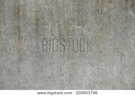 A gray stone texture from a part of a grated concrete wall