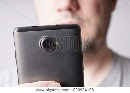 close-up of unrecognizable middle aged man looking at mobile smartphone with shallow depth of field