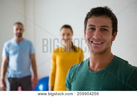 Portrait of man with yoga instructor and woman in health club