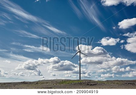 Windmill for electric power production. Wind generator turbine and blue sky with clouds in Iceland- ecology energy saving concept